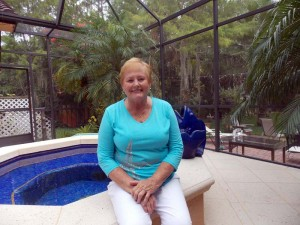 Sandra Mathies sits by her spa with a view of her lush property behind her.
